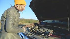 Κλείστε επάνω το κορίτσι προσπαθεί να σκάψει κάτω από την κουκούλα του αυτοκινήτου ψάχνει ένα ελάττωμα αλλά δεν ξέρει ακριβώς πού απόθεμα βίντεο