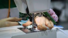 Κλείστε επάνω: το κορίτσι ράβει στη ράβοντας μηχανή Βάζει τον ιστό κάτω από τη βελόνα απόθεμα βίντεο