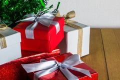 Κλείστε επάνω το κόκκινο και άσπρο κιβώτιο δώρων στον ξύλινο πίνακα με το δέντρο πεύκων και το υπόβαθρο κώνων πεύκων Στοκ φωτογραφίες με δικαίωμα ελεύθερης χρήσης
