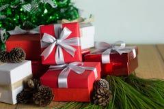 Κλείστε επάνω το κόκκινο και άσπρο κιβώτιο δώρων στον ξύλινο πίνακα με το δέντρο πεύκων και το υπόβαθρο κώνων πεύκων Στοκ Φωτογραφίες