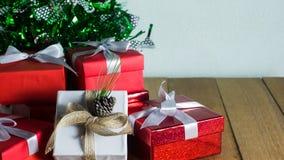 Κλείστε επάνω το κόκκινο και άσπρο κιβώτιο δώρων στον ξύλινο πίνακα με το δέντρο πεύκων και το υπόβαθρο κώνων πεύκων Στοκ Φωτογραφία