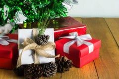 Κλείστε επάνω το κόκκινο και άσπρο κιβώτιο δώρων στον ξύλινο πίνακα με το δέντρο πεύκων και το υπόβαθρο κώνων πεύκων Στοκ φωτογραφία με δικαίωμα ελεύθερης χρήσης