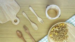 Κλείστε επάνω το κύπελλο granola με ένα ξύλινο κουτάλι και το πιάτο σε ένα ξύλινο επιτραπέζιο υπόβαθρο r απομονωμένος στο λευκό Έ στοκ εικόνες με δικαίωμα ελεύθερης χρήσης