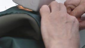 Κλείστε επάνω το μήκος σε πόδηα ενός επαγγελματικού ράφτη γυναικών που ράβει ένα βαμβάκι ντύνει με μια ράβοντας μηχανή φιλμ μικρού μήκους
