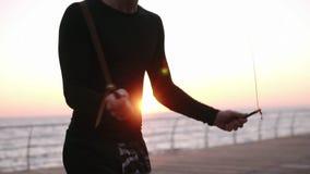 Κλείστε επάνω το μήκος σε πόδηα του κορμού του καυκάσιου άλματος αθλητών πέρα από το σχοινί εκσκαφέων υπαίθρια μαύρο sportswear Ο φιλμ μικρού μήκους