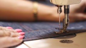 Κλείστε επάνω το μακρο πυροβολισμό των θηλυκών χεριών που λειτουργούν στο πόδι και τη βελόνα ράβοντας μηχανών presser πλησίον Καυ φιλμ μικρού μήκους