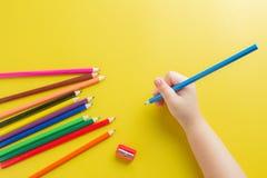 Κλείστε επάνω το μολύβι χρώματος εκμετάλλευσης χεριών μικρών κοριτσιών με κίτρινο Backg Στοκ Φωτογραφίες