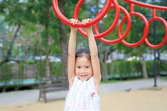Κλείστε επάνω το παιχνίδι μικρών κοριτσιών στο γυμναστικό δαχτυλίδι στην παιδική χαρά υπαίθρια στοκ εικόνα με δικαίωμα ελεύθερης χρήσης