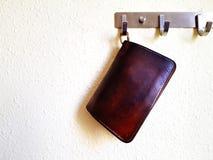 Κλείστε επάνω το παλαιό εκλεκτής ποιότητας καφετί πορτοφόλι δέρματος που κρεμιέται στις κρεμάστρες χάλυβα στον άσπρο τοίχο με το  Στοκ Φωτογραφία