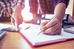 Κλείστε επάνω το περιστασιακό επιχειρησιακό άτομο που υπογράφει τη σύμβαση που αναλύει τα στοιχεία στοκ εικόνες