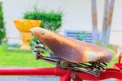 Κλείστε επάνω το ποδήλατο σελών δέρματος που ο κόκκινος κλασικός τρύγος προηγούμενο σε όμορφο με το διάστημα αντιγράφων για προσθ στοκ εικόνα