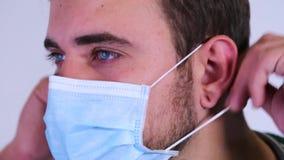 Κλείστε επάνω το πορτρέτο ενός αρσενικού προσώπου χειρούργων ` s που τίθεται σε μια χειρουργική μάσκα φιλμ μικρού μήκους