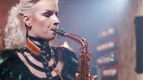 Κλείστε επάνω το πορτρέτο ενός θηλυκού saxophonist σε μια ζωντανή συναυλία τζαζ φιλμ μικρού μήκους