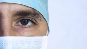 Κλείστε επάνω το πορτρέτο ενός χειρούργου ή ενός γιατρού με τη μάσκα και μιας κάσκας έτοιμης για τη λειτουργία στο νοσοκομείο ή τ απόθεμα βίντεο
