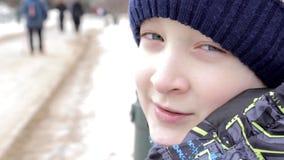 Κλείστε επάνω το πορτρέτο ενός όμορφου το αγόρι με τα καταπληκτικά μάτια που κάθεται σε έναν πάγκο στο πάρκο το χειμώνα φιλμ μικρού μήκους