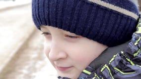 Κλείστε επάνω το πορτρέτο ενός όμορφου το αγόρι με τα καταπληκτικά μάτια που κάθεται σε έναν πάγκο στο πάρκο το χειμώνα απόθεμα βίντεο