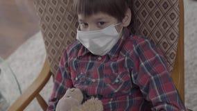 Κλείστε επάνω το πορτρέτο λίγη ανεπαρκής συνεδρίαση αγοριών στην πολυθρόνα με μια ιατρική μάσκα στο πρόσωπό του που κρατά το παιχ απόθεμα βίντεο