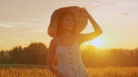 Κλείστε επάνω το πορτρέτο μιας ευτυχούς χαμογελώντας γυναίκας με μακρυμάλλη στο καπέλο περπατώντας στον τομέα σίτου απόθεμα βίντεο