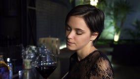 Κλείστε επάνω το πορτρέτο μιας ζαλίζοντας νέας γυναίκας brunette που απολαμβάνει τα ποτά στο φραγμό το βράδυ απόθεμα βίντεο