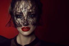 Κλείστε επάνω το πορτρέτο μιας όμορφης κυρίας με τα ζωηρά μπλε μάτια και τελειοποιήστε αποτελεί το κρύψιμο του προσώπου της πίσω  στοκ φωτογραφία με δικαίωμα ελεύθερης χρήσης