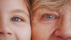 Κλείστε επάνω το πορτρέτο της γιαγιάς και της εγγονής μπλε φωτεινά μάτια απόθεμα βίντεο