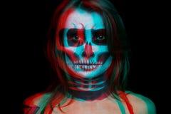 Κλείστε επάνω το πορτρέτο της γυναίκας με το κρανίο αποκριών αποτελεί πέρα από το μαύρο υπόβαθρο η επίδραση μετατόπισης χρώματος  στοκ φωτογραφία