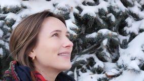 Κλείστε επάνω το πορτρέτο της ελκυστικής γυναίκας που εξετάζει κάτι στο χειμερινό πάρκο φιλμ μικρού μήκους