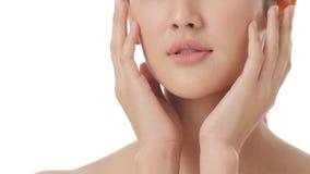 Κλείστε επάνω το πορτρέτο της όμορφης νέας ασιατικής γυναίκας σχετικά με το πρόσωπο και του υγιούς δέρματος στη σε αργή κίνηση έν απόθεμα βίντεο