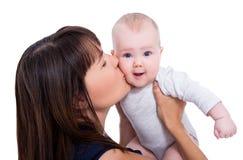 Κλείστε επάνω το πορτρέτο της όμορφης νέας μητέρας που φιλά λίγο μωρό Στοκ Εικόνες
