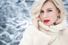 Κλείστε επάνω το πορτρέτο της όμορφης ξανθής μπλε-eyed κυρίας με τέλειο αποτελεί το κράτημα ενός περιλαίμιου του πολυτελούς παλτο στοκ εικόνα με δικαίωμα ελεύθερης χρήσης