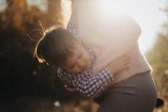Κλείστε επάνω το πορτρέτο του γιου Χαρούμενα χέρια εκμετάλλευσης μητέρων και περιστροφή του γιου της στο δασικό ευτυχές αγόρι που στοκ εικόνα