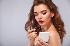 Κλείστε επάνω το πορτρέτο του ελκυστικού κοριτσιού που τα χείλια της Κρατά το κόκκινο κραγιόν στο ποντίκι Απομονωμένος σε γκρίζο στοκ φωτογραφία με δικαίωμα ελεύθερης χρήσης