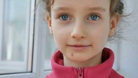 Κλείστε επάνω το πορτρέτο του λίγο ξανθού κοριτσιού στο κόκκινο πουκάμισο που τρώει το φωτεινό πράσινο microgreens του ηλίανθου Π απόθεμα βίντεο