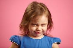 Κλείστε επάνω το πορτρέτο του μικρού κοριτσιού που τρία έτη απομονωμένο στο ροζ υπόβαθρο, εκφράζουν την απογοήτευση ή τη δυσαρέσκ στοκ εικόνα