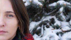 Κλείστε επάνω το πορτρέτο του μισού προσώπου γυναικών εξετάζοντας τη κάμερα το χειμώνα φιλμ μικρού μήκους