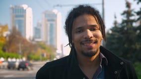Κλείστε επάνω το πορτρέτο του νέου τύπου αφροαμερικάνων με τα dreadlocks χαμογελώντας ήρεμα στη κάμερα στο οδικό υπόβαθρο απόθεμα βίντεο
