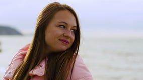 Κλείστε επάνω το πορτρέτο του νέου χαμόγελου γυναικών με την καφετιά τρίχα που φυσά στον αέρα κοιτάζοντας arround απόθεμα βίντεο