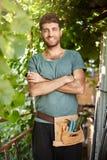 Κλείστε επάνω το πορτρέτο του νέου όμορφου γενειοφόρου κηπουρού με τα εργαλεία κήπων που χαμογελά, που στέκονται στη σκιά δέντρων στοκ εικόνες