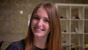 Κλείστε επάνω το πορτρέτο του χαμογελώντας κοριτσιού πιπεροριζών στο γραφείο, το οποίο προσέχει στη κάμερα και κοιτάζει μακριά φιλμ μικρού μήκους