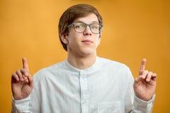 Κλείστε επάνω το πορτρέτο του όμορφου ατόμου στα γυαλιά με τα αυξημένα δάχτυλα στοκ φωτογραφία