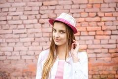 Κλείστε επάνω το πορτρέτο του όμορφου μοντέρνου κοριτσιού παιδιών στο καπέλο κοντά στο ρόδινο τουβλότοιχο ως υπόβαθρο στοκ φωτογραφίες