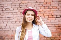 Κλείστε επάνω το πορτρέτο του όμορφου μοντέρνου κοριτσιού παιδιών στο καπέλο κοντά στο ρόδινο τουβλότοιχο ως υπόβαθρο στοκ εικόνα με δικαίωμα ελεύθερης χρήσης
