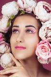 Κλείστε επάνω το πορτρέτο του όμορφου νέου κοριτσιού με το ρόδινο λουλούδι τριαντάφυλλων στο κεφάλι και αποτελέστε στοκ φωτογραφίες με δικαίωμα ελεύθερης χρήσης