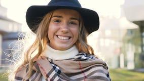 Κλείστε επάνω το πορτρέτο του όμορφου νέου περπατήματος γυναικών, να φανεί ευθύς στη κάμερα και του χαμόγελου φιλμ μικρού μήκους