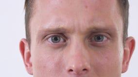 Κλείστε επάνω το πρόσωπο του ατόμου που κοιτάζει κεκλεισμένων των θυρών με το θυμό Βλάστηση σε μια άσπρη ανασκόπηση φιλμ μικρού μήκους