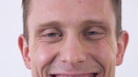 Κλείστε επάνω το πρόσωπο του ευτυχούς smilling ατόμου που φαίνεται κεκλεισμένων των θυρών απομονωμένος σε ένα άσπρο υπόβαθρο απόθεμα βίντεο