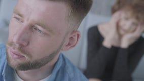 Κλείστε επάνω το πρόσωπο του λυπημένου δυστυχισμένου νεαρού άνδρα που κοιτάζει μακριά στο πρώτο πλάνο Ο θολωμένος αριθμός της ώρι απόθεμα βίντεο