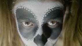 Κλείστε επάνω το πρόσωπο του νέου κοριτσιού που φορούν το χρώμα κρανίων αποκριών makeup και του κοστουμιού ευθύς στη κάμερα - απόθεμα βίντεο