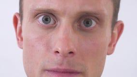 Κλείστε επάνω το πρόσωπο του τρελλού ατόμου με τα γκρίζα μάτια που φαίνεται κεκλεισμένων των θυρών με το θυμό Βλάστηση σε μια άσπ φιλμ μικρού μήκους