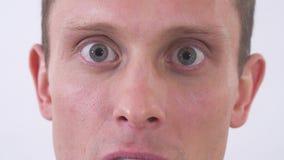 Κλείστε επάνω το πρόσωπο του τρελλού ατόμου που φαίνεται κεκλεισμένων των θυρών με το θυμό Βλάστηση σε μια άσπρη ανασκόπηση φιλμ μικρού μήκους